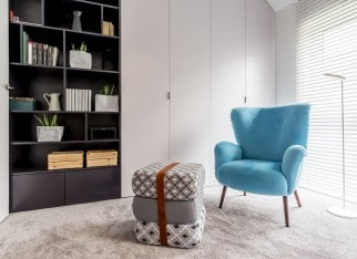 Modern interior with cozy reading corner with black bookcase, blue armchair, pouf and big window with blinds