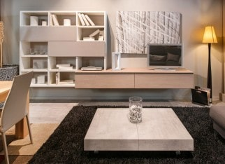 Modern living room interior with dining table open plan to a lounge area with bookcase, television, coffee table and sofa illuminated by a standing corner lamp