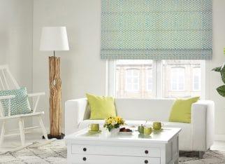 Nowoczesny salon w zieleni. Świeże wnętrze z z zaakcentowanymi zielonymi dodatkami w postaci rolety rzymskiej, poduszek dekoracyjnych oraz ceramicznych filiżanek. Białe meble w postaci stolika, sofy i dywanu stanowią idealne tło dla nowoczesnych, odważnych tkanin.