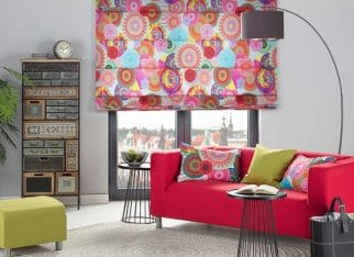 Barwny i energetyzujący salon w stylu boho, w którym wykorzystana została tkanina w mandale z kolekcji Comics. Kolorowa roleta rzymska i intensywny czerwony pokrowiec na sofę nadają wnętrzu niepowtarzalny, odwazny charakter. Uzupełnienie stanowią zielone dodatki oraz nowoczesne, surowe meble.