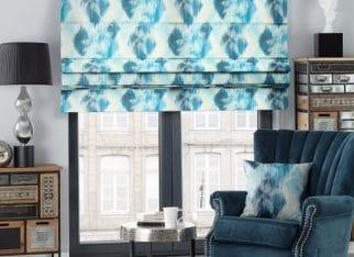 Elegancki salon w nowoczesnym wydaniu. Dominujacym kolorem we wnętrzu jest niebieski, który znajduje się na ekskluzywnym, aksamitnym fotelu oraz na rolecie rzymskiej z kolekcji tkanin Aquarelle. Aranżację uzupełniają nietypowe meble z kolekcji Thais.