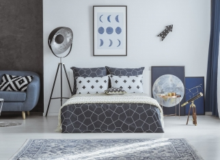 Patterned pillow on blue couch in spacious bedroom interior with telescope and lamp near bed