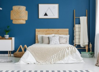 Knit blanket on wooden bed in blue bedroom interior with poster on the wall and lamp