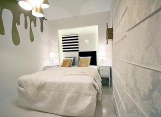 Wąska sypialnia w bieli i złocie