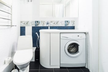 Modern bathroom with shiny white cabinets and washing machine