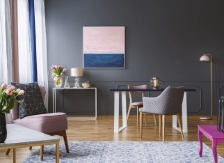 Pink and navy blue painting in grey living room interior with flowers and armchair. Real photo
