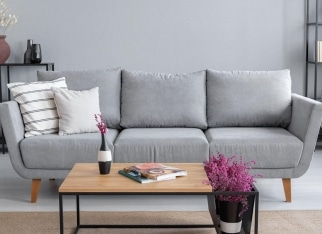 Real photo of a grey sofa, coffee table and lavender flower in a living room interior