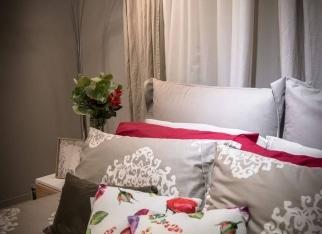 Bedroom interior in soft light with colorful pillows. Modern lamp and vase of fake flowers on the bedside table.