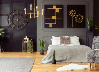 Real photo of golden accents, clock, paintings, plants and double bed in a dark bedroom interior