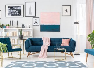 Gold table in front of a navy blue couch with pink blanket in elegant living room interior with painting