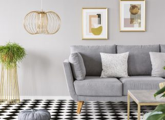Real photo of a living room interior with gold posters on the walls, grey sofa with cushions and checkered floor