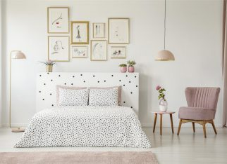 Pastel lamp above table with flower and pink armchair in woman's bedroom interior with bed