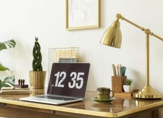 Gold lamp, laptop and plant on wooden desk in white freelancer's interior with poster. Real photo