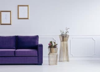 Plants next to purple sofa against grey wall with drawings in gold frames in living room interior