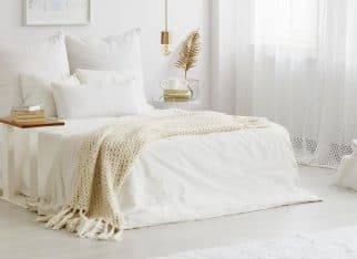 White bedroom interior with windows, gold accessories and white bedsheets on king-size bed