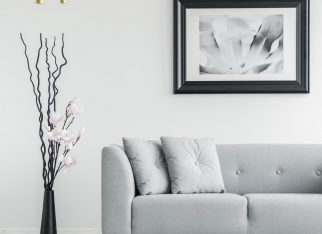 Plant next to grey couch in living room interior with checkered floor and poster. Real photo