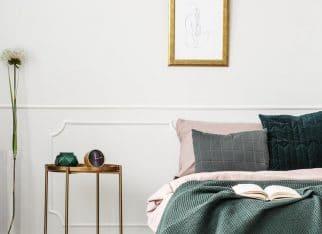 Golden, metal bedside table with clock standing in elegant female bedroom interior