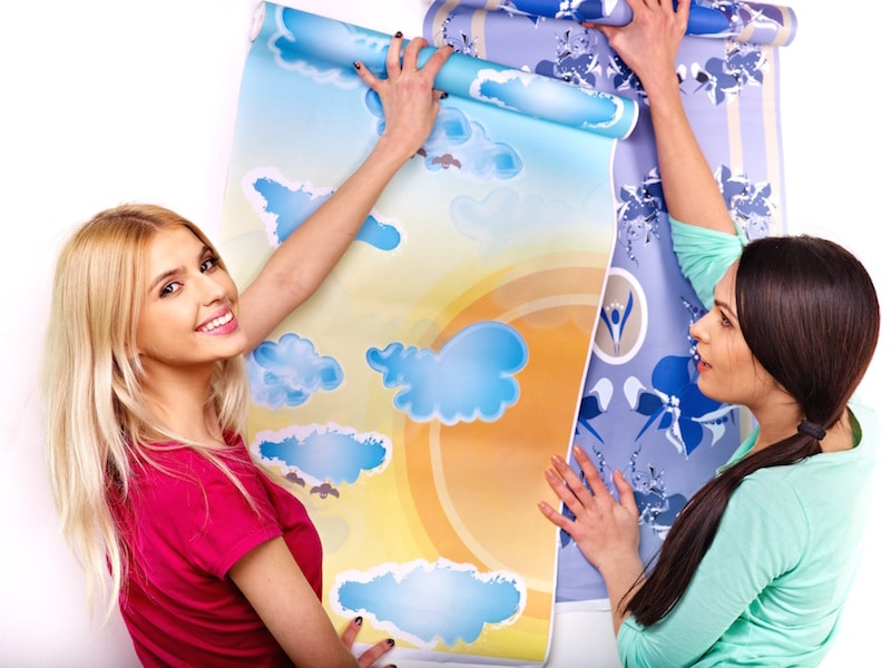 Women glues wallpaper at home