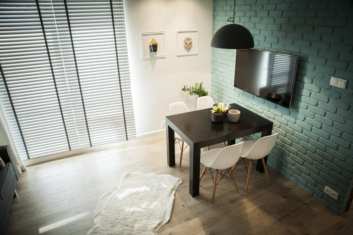 Zobacz pomysłową aranżację salonu z kolorową cegłą w roli głównej.