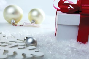 Decorative white gift box with a red bow a background bokeh.