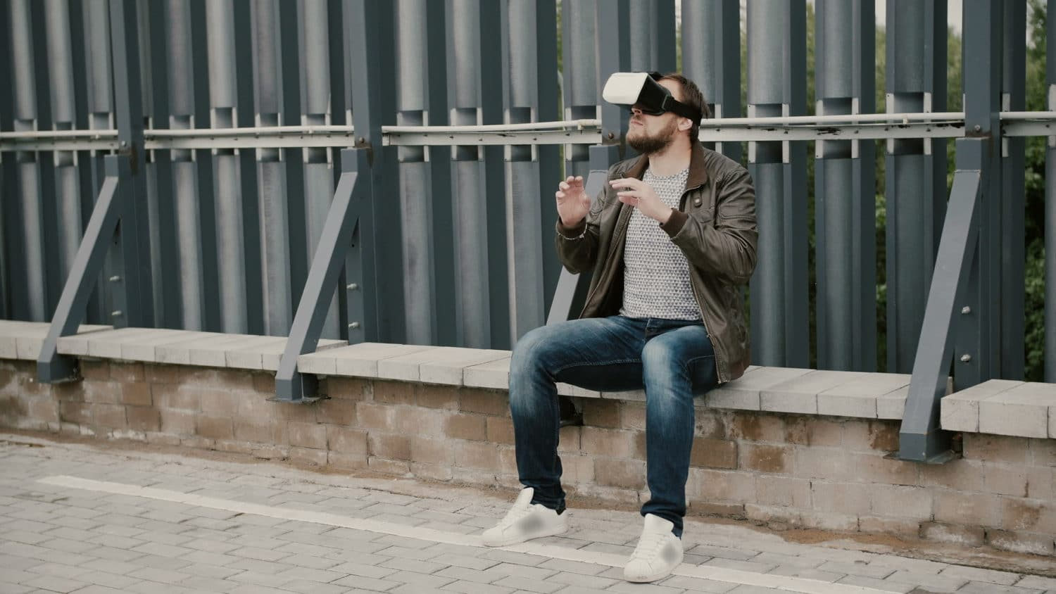 bearded attractive man uses virtual reality glasses on the roof, takes off his glasses and walks away